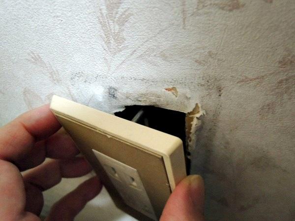 コンセントカバーが壁から外れて穴が開いている